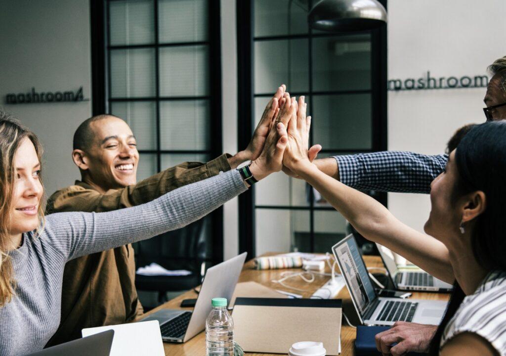 Neljä ihmistä lyö kätensä yhteen työpöydän äärellä.