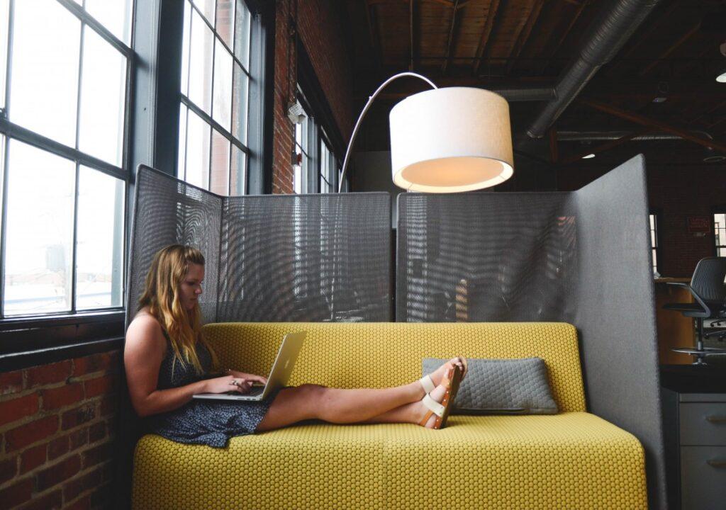 Nainen työskentelemässä keltaisella sohvalla kannettava tietokone sylissään.