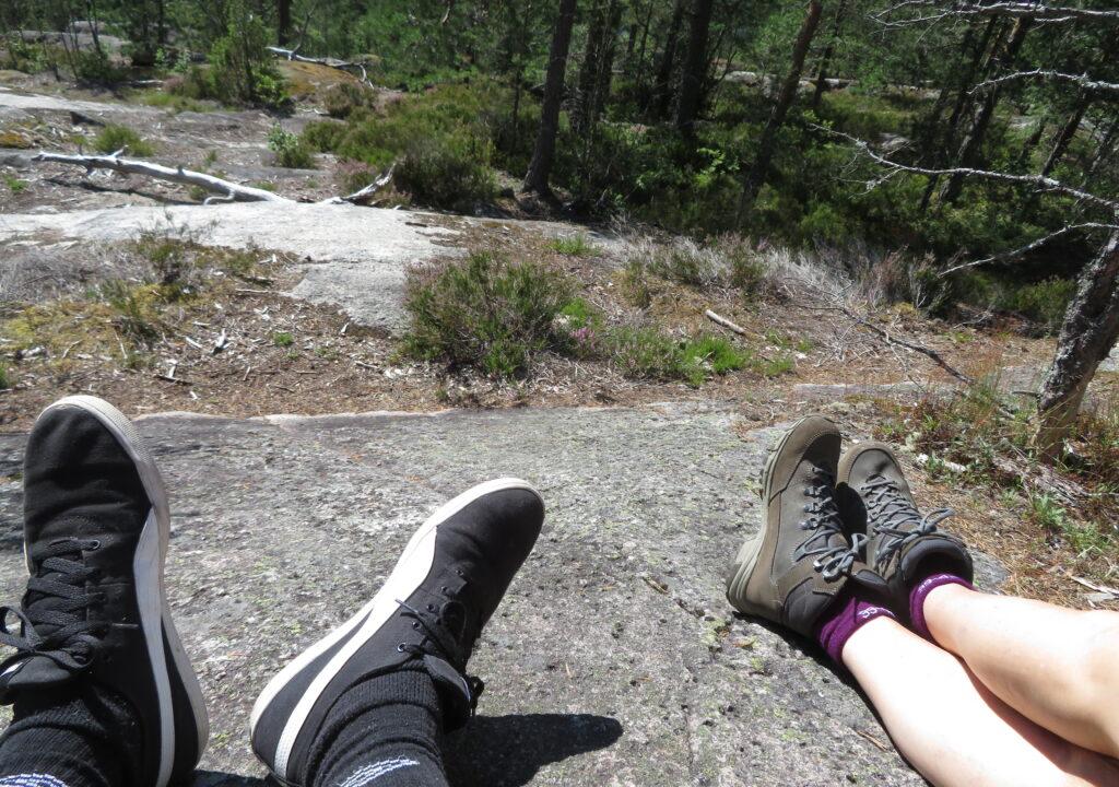 Kuvituskuva kallioilla istuvien henkilöiden jaloista