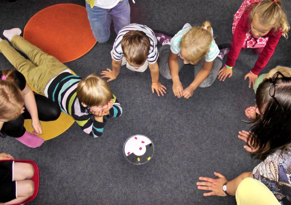 Kuvituskuva, jossa lapsia ringissä pelin ympärillä