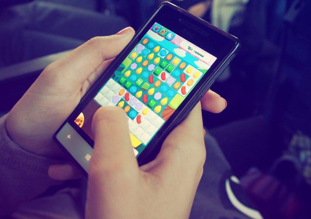 Kuvituskuva henkilön kädessä olevasta puhelimesta, jossa näkyy peli