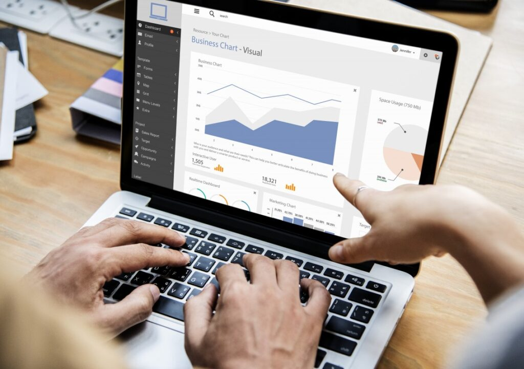 Kuvituskuva, jossa näkyy tietokoneen ruudulla erilaisia tilastoja. Yhden ihmisen kädet työskentelevät näppäimistöllä ja toisen ihmisen käsi osoittaa tilastoja.