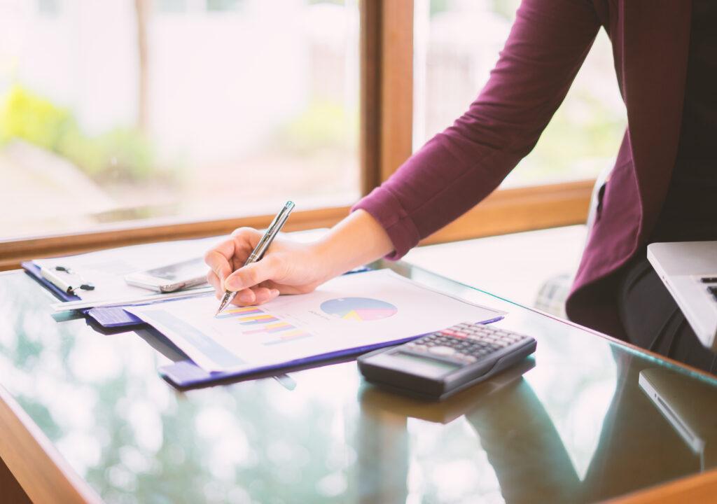 Kuvituskuva jossa näkyy pöydällä olevalle paperille kirjoittava käsi. Pöydällä on myös taskulaskin.