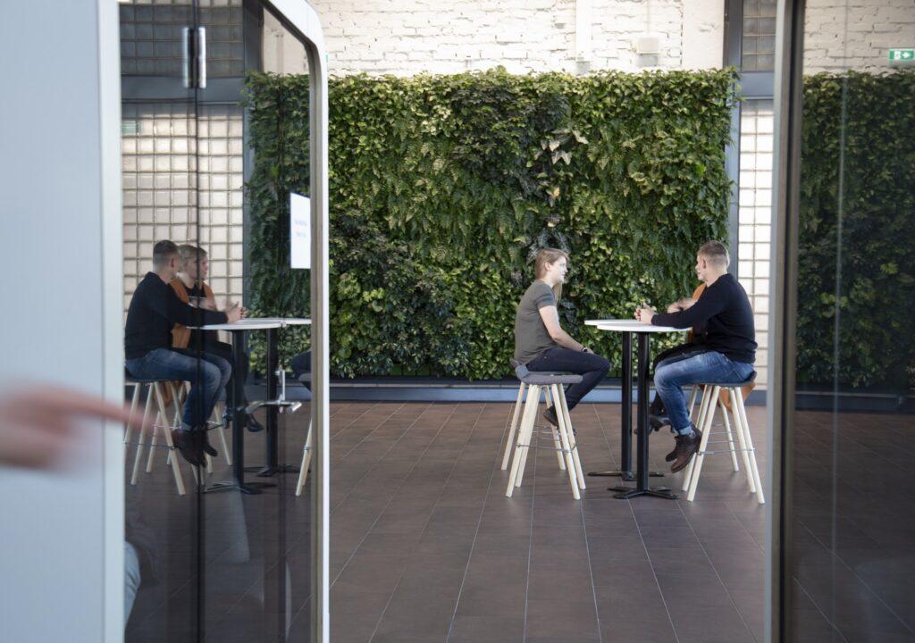 Opiskeljoita istumassa pöydän äärellä, takana viherseinä.