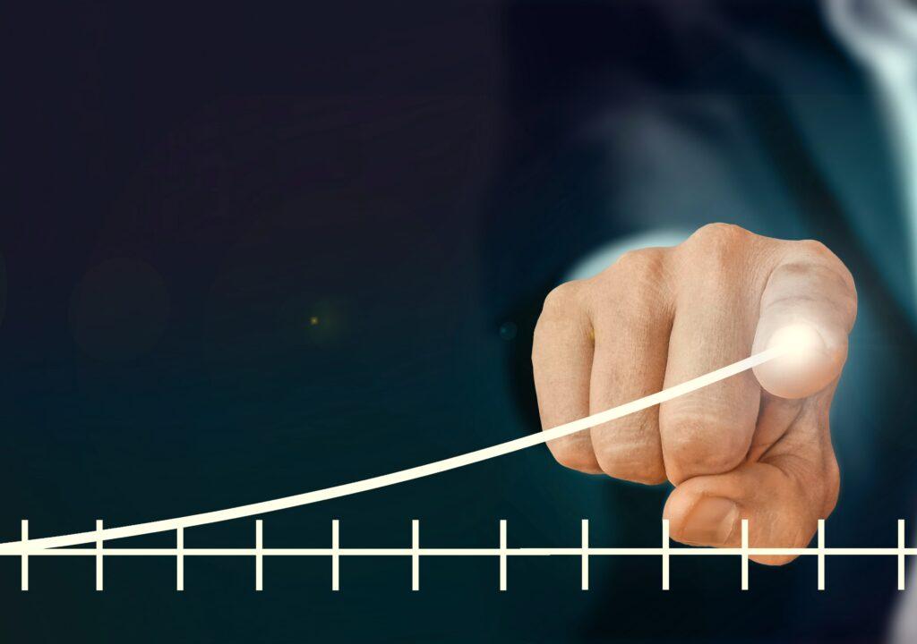 Kuvituskuva, jossa käden etusormi piirtää tilastokuvaajalla viivaa ylöspäin menestyksen merkiksi.en