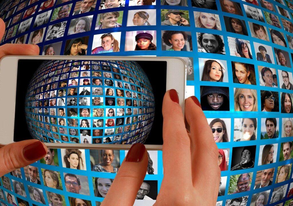 Kuvituskuva, jossa näkyvät kännykkää pitävät kädet ja taustalla kuvayhdistelmä ihmisten kasvoista