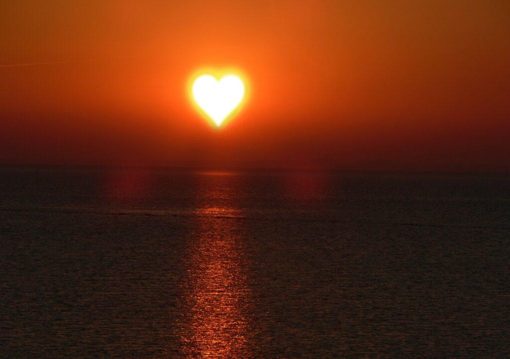 Kuvituskuva tyynestä järven tai meren pinnasta. Kuvassa on joko aamu- tai iltahämärä. Horisontisa loistaa sydämenmuotoinen keltainen aurinko.