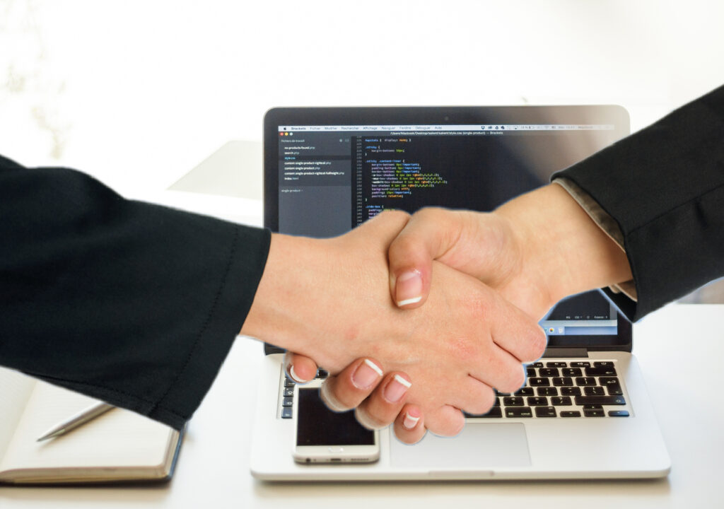 Kuvituskuva jossa kaksi kättä kättelevät. Taustalla näkyy kannettava tietokone.