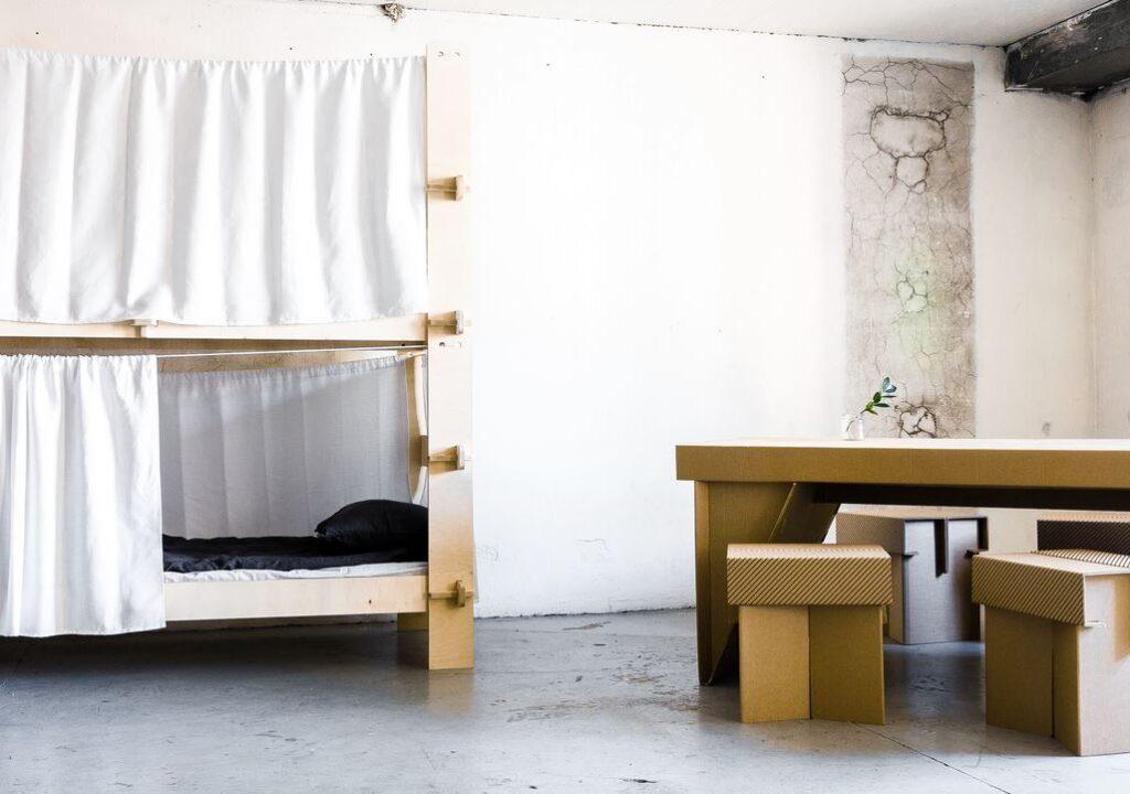 Kuvassa on huone, jossa on kerrpssänky sekä pahvista tehdyt pöytä ja neljä tuolia.