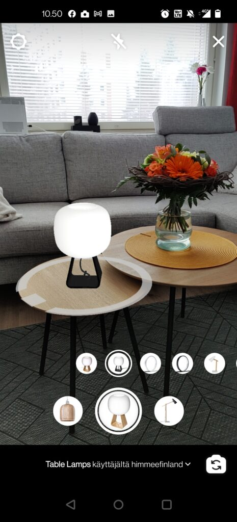 Kuvassa on olohuone, jossa on sohva ikkunan edessä sekä kaksi pientä pyöreätä pöytää. Toisella pöydällä on päällä olevan lamppu ja toisella kukkakimppu.