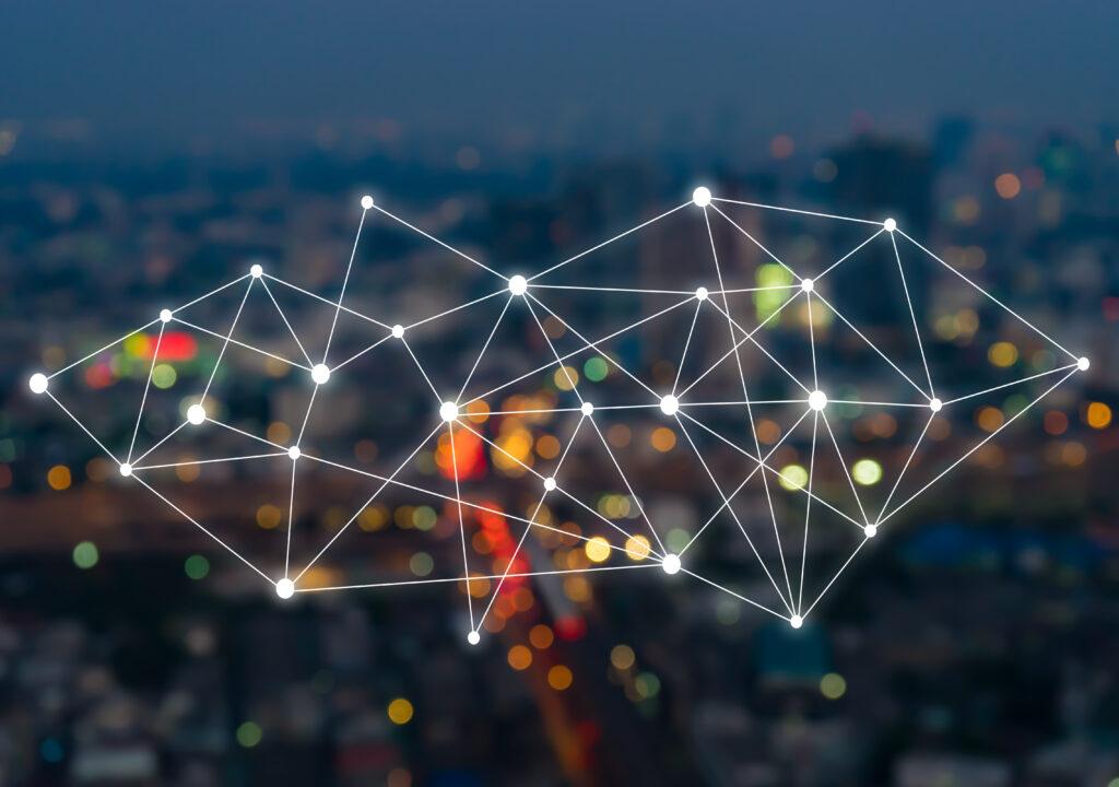 Kuvituskuva jossa kuvataan massadatan yhteyksiä ja esineiden internettiä. Kuvassa taustalla sumea kuva öisestä kaupungista joka näkyy kirkkaan verkon takana. Verkko kuvaa tulevaisuuden teknologian digitaalisuutta.