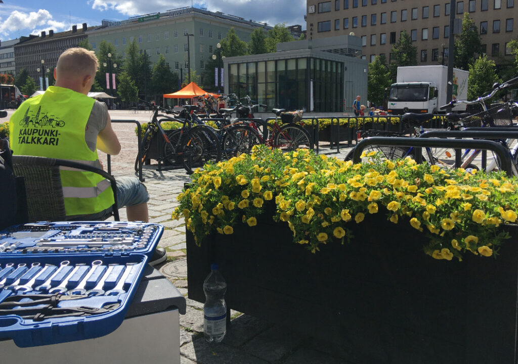 Worker of the guarded bicycle park sitting on a chair, ready to fix bicycles with a visible and open toolbox.