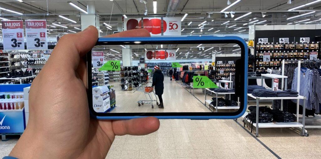Kuvassa näkymä kaupasta. Etualalla käsi pitelee kännykkää, jossa on näytöllä kuva, jossa on vaalenavihreät prosenttimerkinnät nuolella, ja ne osoittavat tarjouksessa olevia tuotteita.