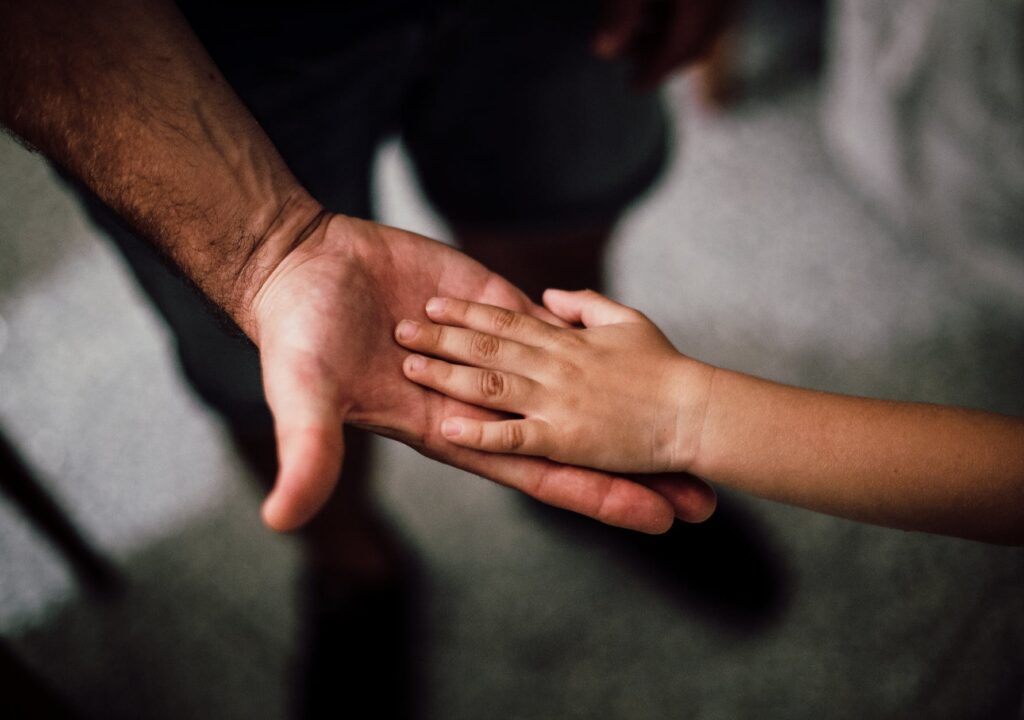 Kuviituskuvassa lapsen käsi lepää miehen kämmenellä.
