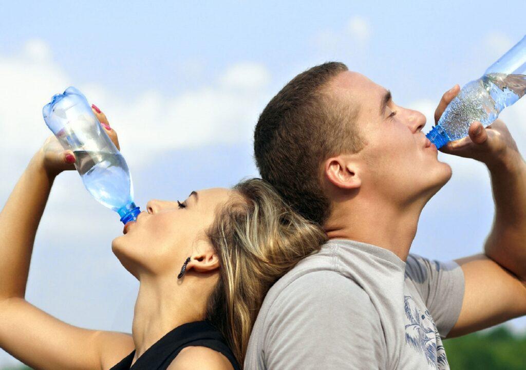Kuvituskuva jossa nainen ja mies ovat selät vastakkain ja juovat pullosta vettä.