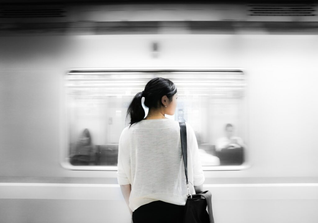 Photo of a woman standing in front of a moving subway train.