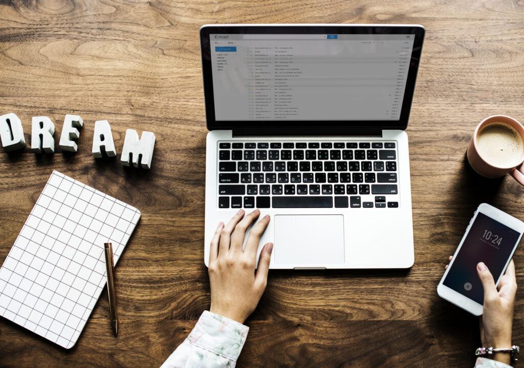 Kuvituskuvassa henkilö, josta näkyy vain kädet, työskentelee laptop-tietokoneella. Toisessa kädessä hänellä on matkapuhelin.
