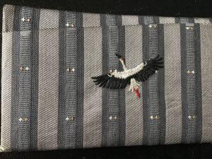Musta-harmaaraidallisesta kankaasta ommeltu käyntikorttikotelo, jossa kirjailtu lentävä haikara.