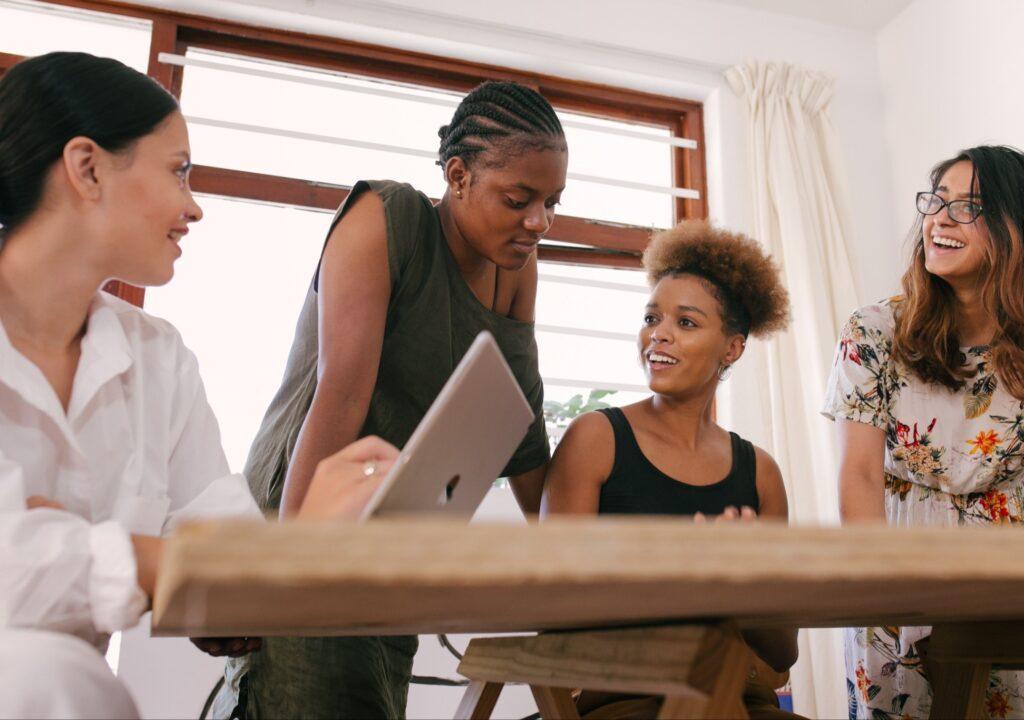 Kuvituskuvassa neljä naista keskustelee pöydän ääressä.