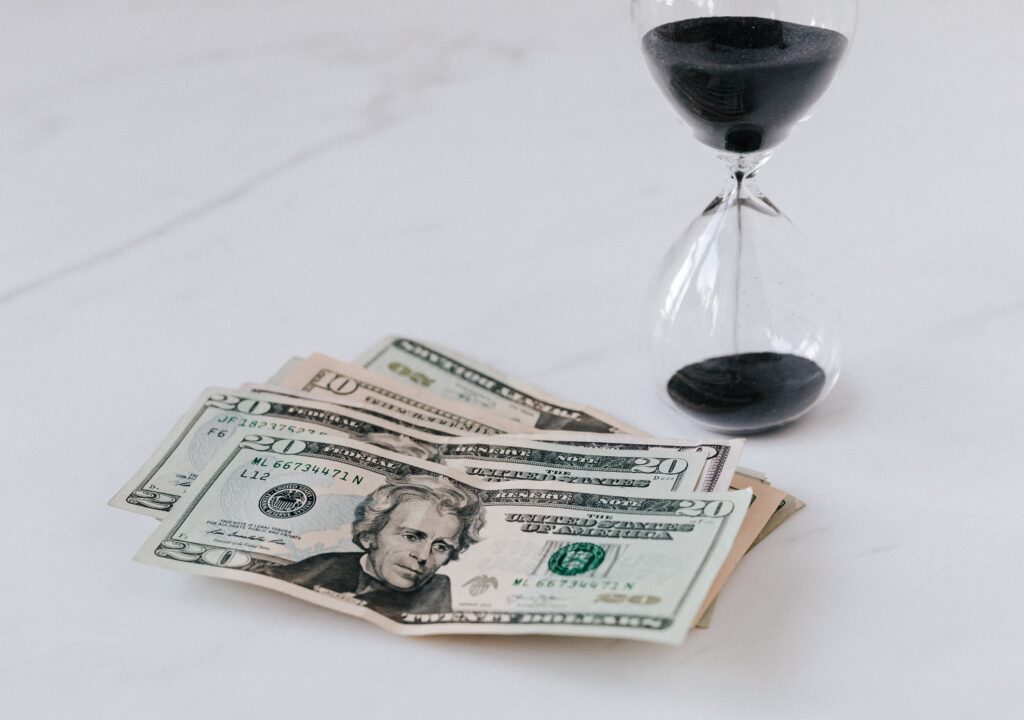 The illustration shows an hourglass and paper money.