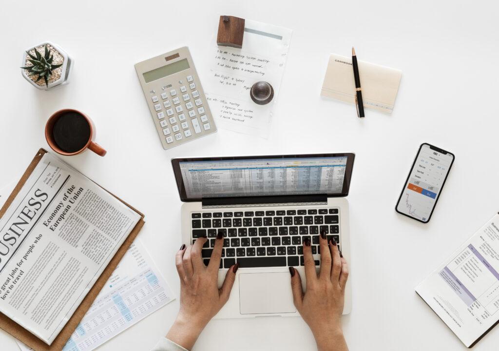 Kuvituskuvassa ihmisen kädet näpyttelevät tietokoneen näppäimistöä ja pöydällä on mysö laskin, paperia ja kynä sekä kahvikuppi.