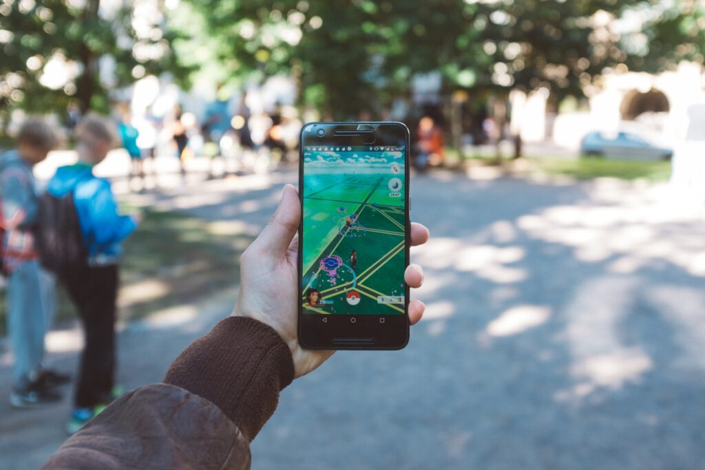 A player holding a smartphone and playing Pokémon Go.