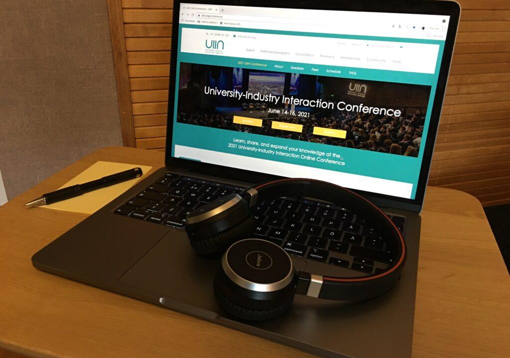 Kuvituskuvassa tietokone, jonka ruudulla näkyy artikkelissa esiteltävän konfrenssin pääsivu. Näppäimistön päällä on kuulokkeet.