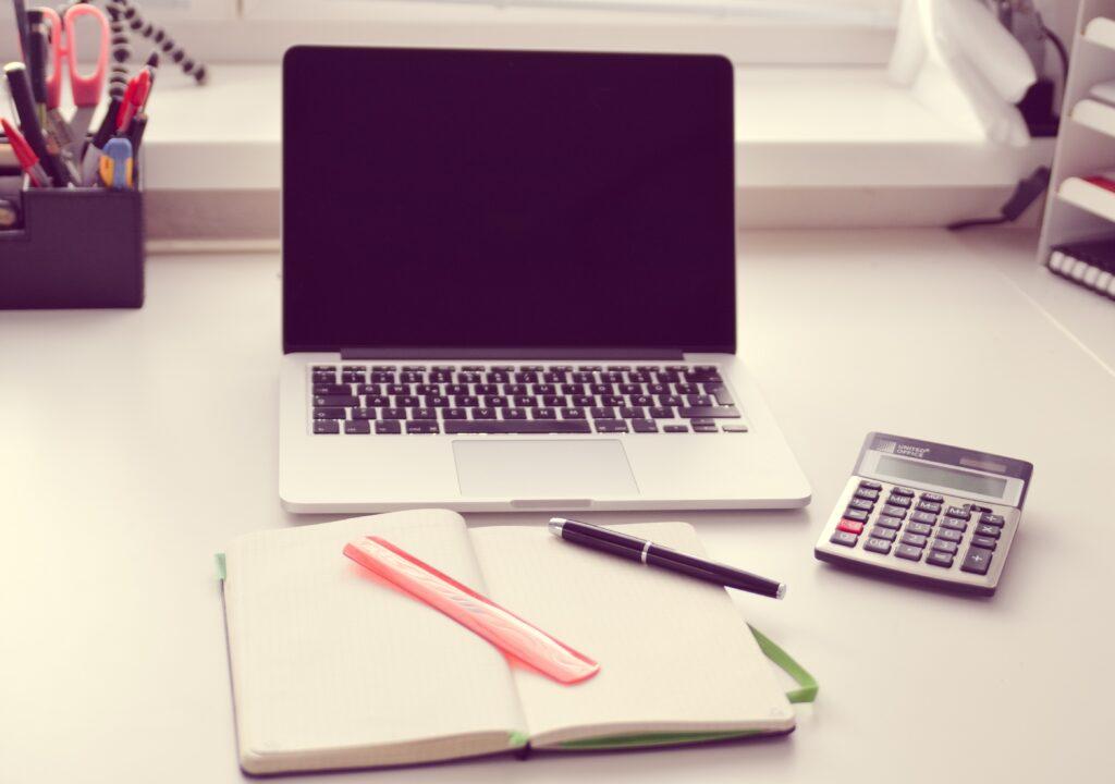 Kuvituskuvassa näkyy tietokone, laskin sekä avattu muistilehtiö.