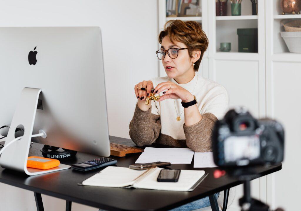 Nainen istuu tietokoneen takana ja puhuu ruudulle, etualalla kamera tallentaa tilannetta.