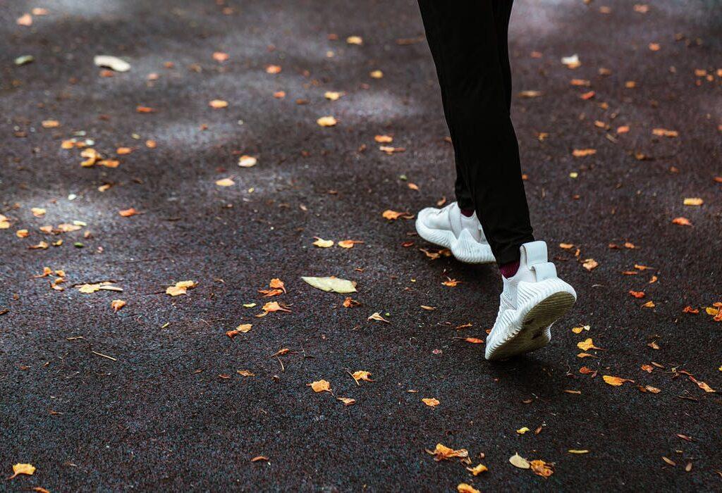 Kuvituskuvassa henkilö juoksee asflatilla, jolle pudonnut keltaisia lehtiä.