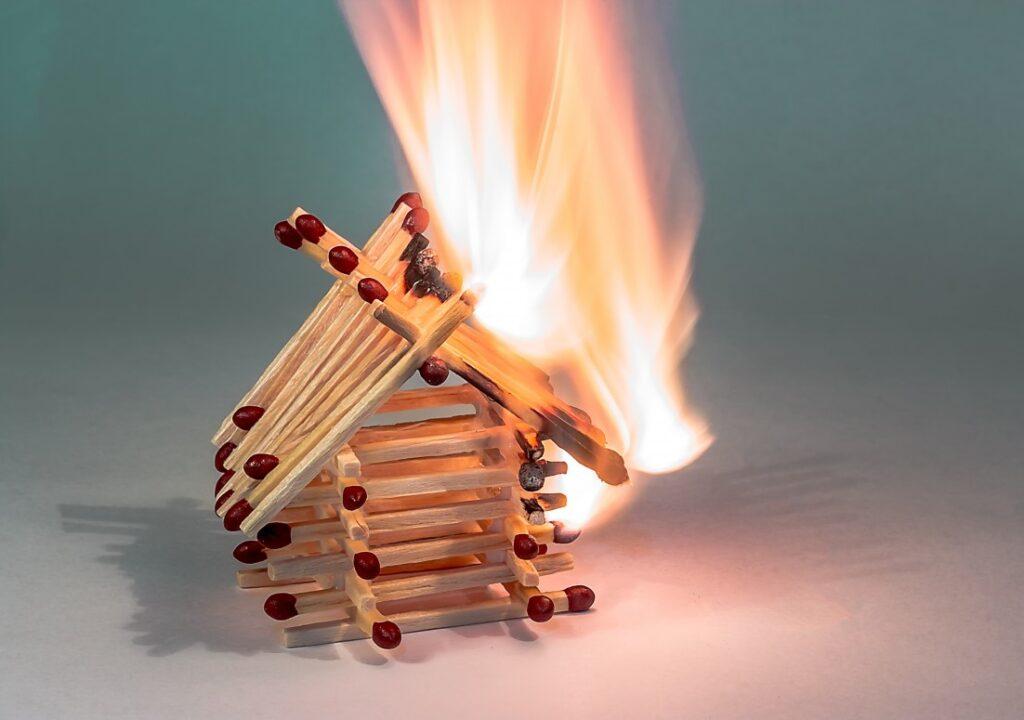 Kuvituskuvassa tulitikuista tehty talo palaa.