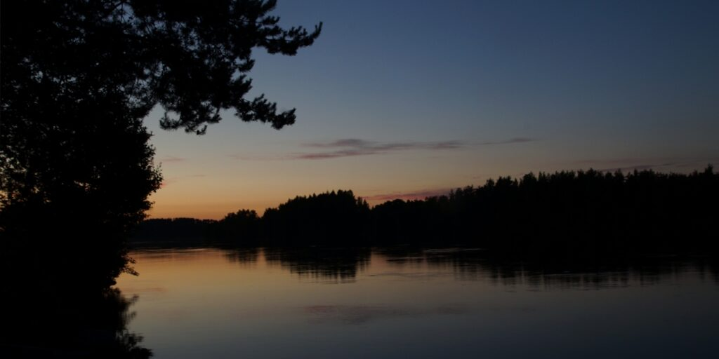 Ilta hämärtyy tyynellä järvellä ja taivas hehkuu oranssisena.